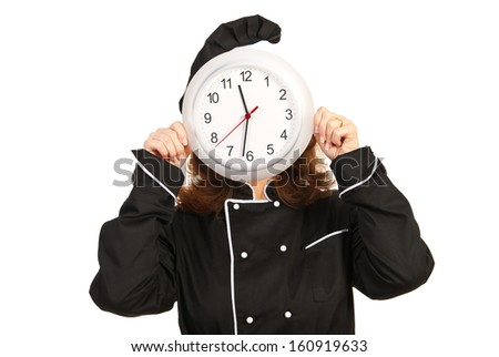 Chef woman in black uniform with face behind clock isolated on white background
