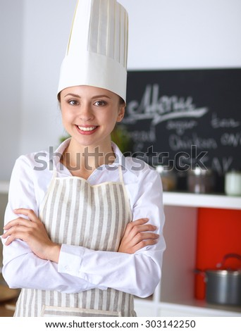 Chef woman portrait with  uniform in the kitchen - stock photo