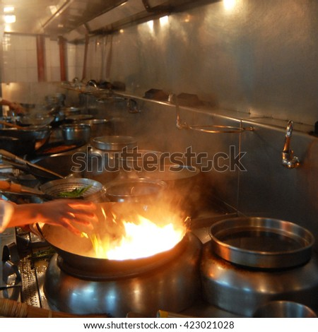 Chef working at a Chinese restaurant kitchen - stock photo