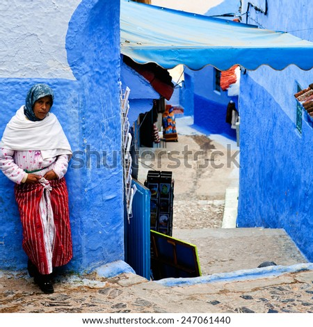 CHEFCHAOUEN, MOROCCO - JANUARY 02: An unidentified Muslim woman standing on the street in ancient blue Medina on January 02, 2014 in Chefchaouen, Morocco - stock photo