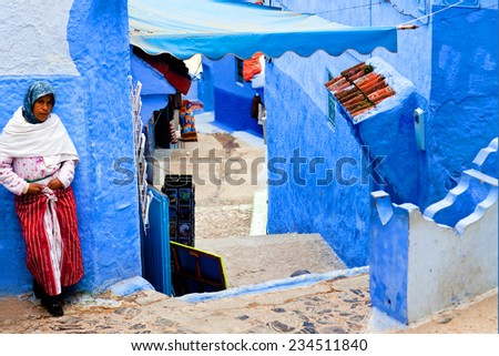 CHEFCHAOUEN, MOROCCO - JANUARY 02: An unidentified Muslim women standing on the street in ancient blue Medina on January 02, 2014 in Chefchaouen, Morocco - stock photo