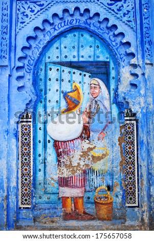 CHEFCHAOUEN, MOROCCO - JANUARY 02: Fresco painting wall at Uta El-Hammam square on January 02, 2014 in Chefchaouen, Morocco. This is the liveliest square in the Chefchaouen medina. - stock photo