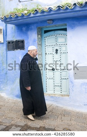 CHEFCHAOUEN, MOROCCO - JANUARY 17, 2010: Unidentified man wearing typical moroccan robe walking down a street of the ancient town of Chefchaouen in Morocco. - stock photo