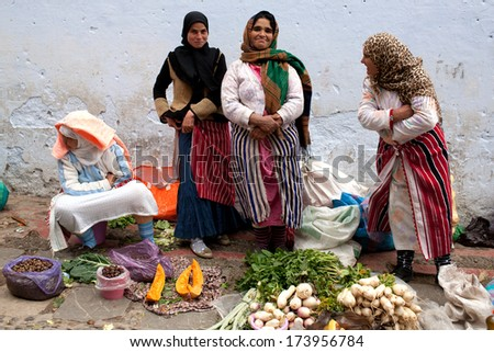 CHEFCHAOUEN, MOROCCO - JANUARY 02: Unidentified smiling women poses for a photo in the souk on January 02, 2014 in Chefchaouen, Morocco. - stock photo