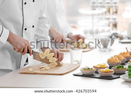 Chefs cutting banana on a wooden boards.