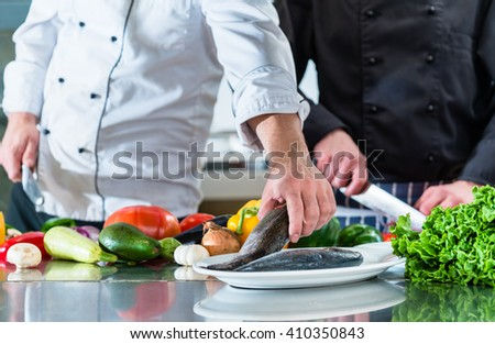 Chefs preparing food in teamwork at restaurant kitchen, cutting vegetables and fish