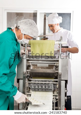 Chefs processing ravioli pasta in machine at commercial kitchen - stock photo