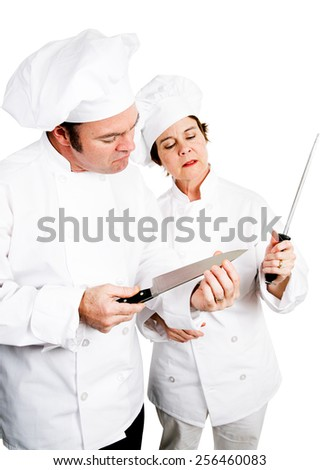 Chefs sharpening and testing the edge of their top quality knives.  Isolated on white.