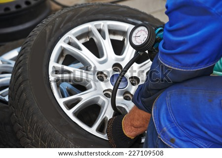 Cheking air pressure in automobile car wheel after tyre fitting or tire replacing for winter type - stock photo