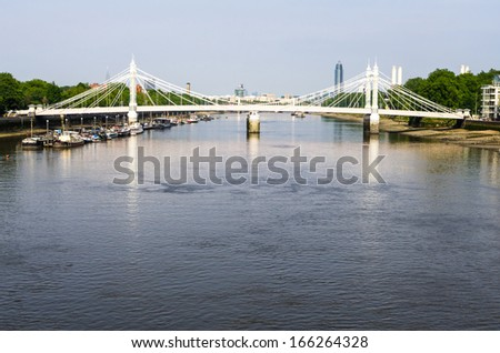Chelsea Bridge over the river Thames in London, Battersea power station in the background  - stock photo