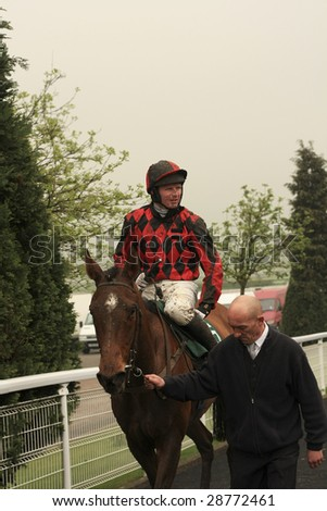 CHELTENHAM, GLOUCS, APRIL 17 2009: Prince of Gdansk and Paul Moloney returning from the second race at the April National Hunt Race Meeting at Cheltenham racecourse, UK - stock photo