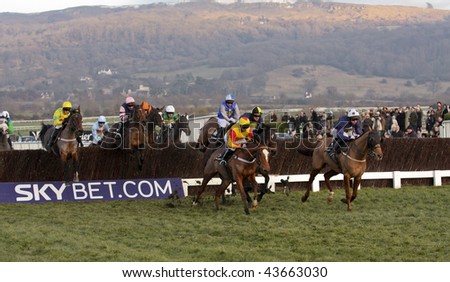 CHELTENHAM, GLOUCS: Jockeys take fences for position in the fourth race at Cheltenham Racecourse January 1, 2010 in Cheltenham, Gloucestershire - stock photo