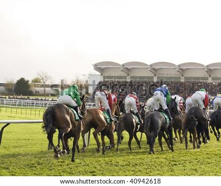 CHELTENHAM, GLOUCS; NOV 14: jockeys race up the hill in the fourth race at Cheltenham Racecourse, UK, November 14, 2009 in Cheltenham, Gloucs - stock photo