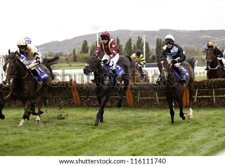 CHELTENHAM, GLOUCS, OCT 19 2012, Jockeys Charlie Poste and Richard Johnson battle over fences in the first race at Cheltenham Racecourse, Cheltenham UK Oct 19 2012 - stock photo