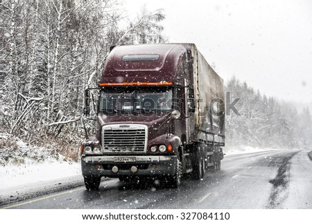 CHELYABINSK REGION, RUSSIA - OCTOBER 11, 2015: Semi-trailer truck Freightliner Century Class at the interurban freeway during a heavy snowfall. - stock photo