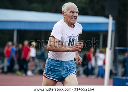 Chelyabinsk, Russia - August 28, 2015:  elderly man runs 400 meters during championship of Russia on track and field athletics among the elderly, Chelyabinsk, Russia - August 28, 2015 - stock photo