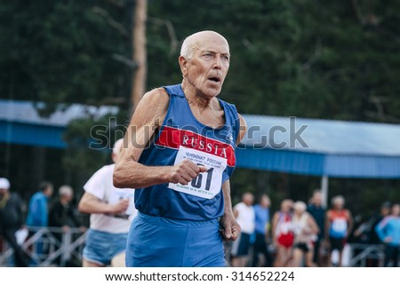 Chelyabinsk, Russia - August 28, 2015:  old man runs 400 meters during championship of Russia on track and field athletics among the elderly, Chelyabinsk, Russia - August 28, 2015 - stock photo