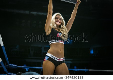 Chelyabinsk, Russia - December 5, 2015: beautiful young girl smiling in ring, shows a sign with round number during Cup of Russia MMA - stock photo