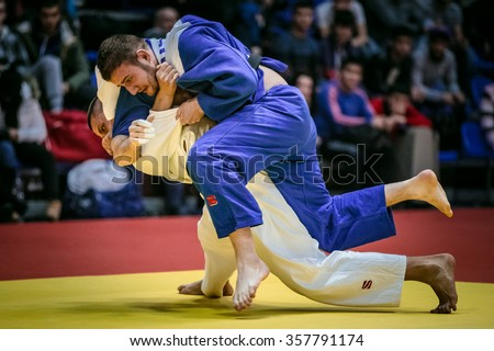 Chelyabinsk, Russia -  December 20, 2015: fight on tatami two male athletes judoists in final. in background fans during All-Russian competition on judo of memory Grigory Verichev - stock photo