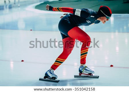 Chelyabinsk; Russia - December 3; 2015: side view young woman athlete speedskater goes around turn sprint distance during Cup of Russia on speed skating