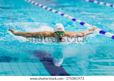 Chelyabinsk, Russia - February 2, 2016: male swimmer athlete swimming butterfly stroke in pool during Championship of Ural Federal District in swimming