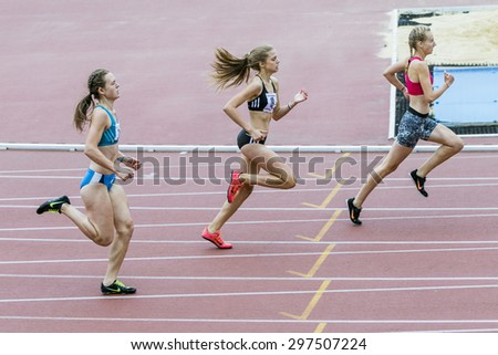 Chelyabinsk, Russia - July 10, 2015: race sprint distance of 400 metres, young women athletes running to finish line during Championship of Chelyabinsk on track and field athletics - stock photo