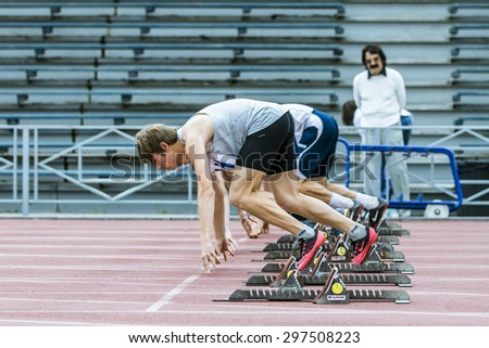 Chelyabinsk, Russia - July 10, 2015: start sprint distance of group young male athletes from starting blocks during Championship of Chelyabinsk on track and field athletics