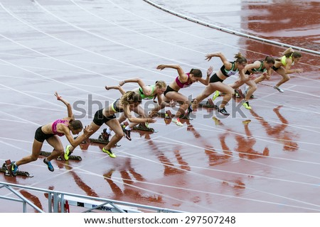 Chelyabinsk, Russia - July 10, 2015: start young women athletes at sprint distance in rain during Championship of Chelyabinsk on track and field athletics - stock photo