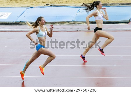 Chelyabinsk, Russia - July 10, 2015: two young girls athletes running to finish line sprint during Championship of Chelyabinsk on track and field athletics - stock photo
