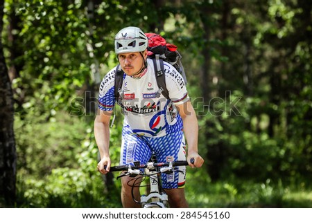 """Chelyabinsk, Russia - May 31, 2015: young man with a backpack, rides a bike through woods during the race """"New Energy 2015"""" - stock photo"""
