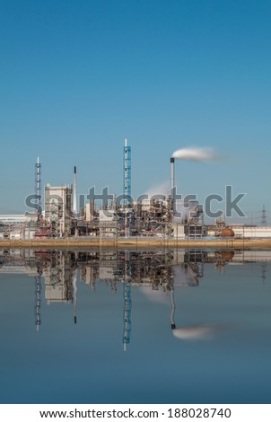 Chemical Factory Exterior with Reflection and Smoke, Day Time Long Exposure. - stock photo