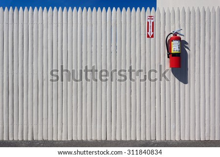 chemical fire extinguisher mounted on a wooden fence - stock photo