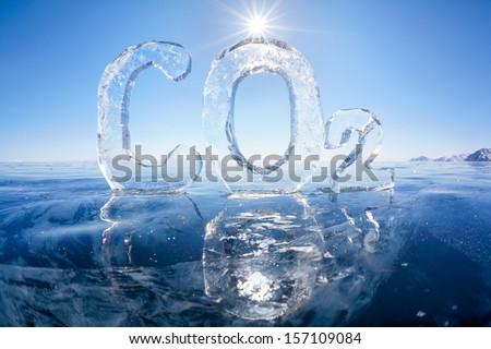 Chemical formula of greenhouse gas carbon dioxide CO2 made from ice on winter frozen lake Baikal under blue sky and Sun rays  - stock photo