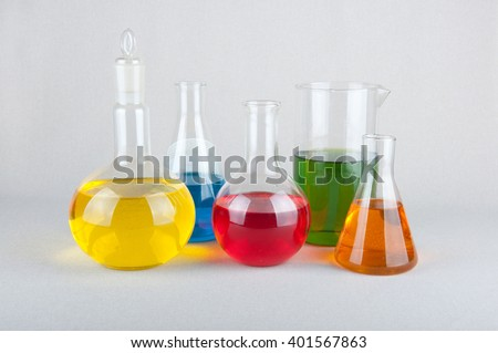 Chemical glasswares with yellow, blue, green, red and orange liquid on white background