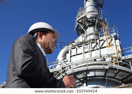 Chemical industrial engineer standing front of large oil industry writing and checking on notepad