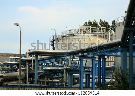 Chemical industry, truck with fuel tank and industrial storage site - stock photo