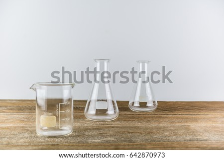 Chemical laboratory glassware with empty Erlenmeyer flask on wooden table