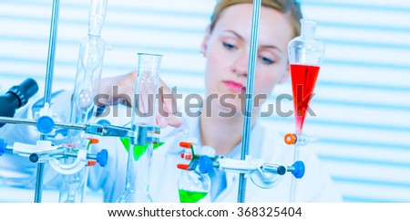 Chemical laboratory scene: attractive young student scientist observing the blue indicator color shift after the solution destillation. - stock photo