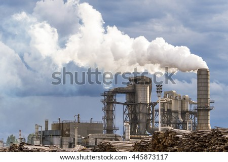 Chemical plant for lumber industry. Silos, chimney, smoke and stormy sky.