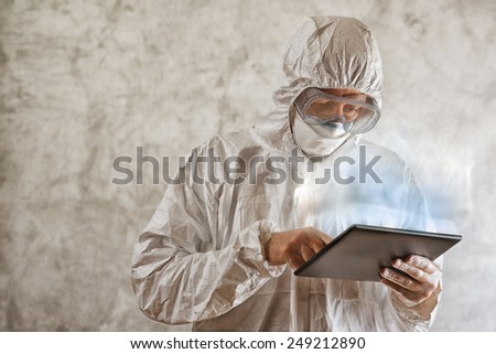 Chemical Scientist in Protective Laboratory Clothing Using Digital Tablet Computer - stock photo
