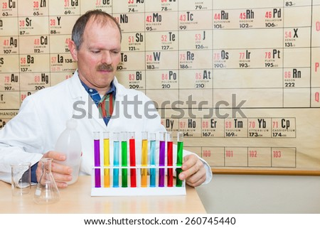 Chemist filling glass test tubes with colored liquids in front of periodic system in classroom - stock photo
