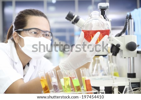 Chemist holding sample of liquid in  lab or laboratory - stock photo