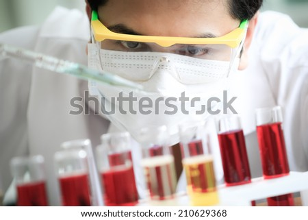 Chemist is analyzing sample in laboratory room.