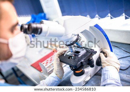 Chemist researcher working with microscope for forensic evidence - stock photo