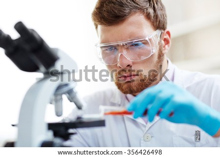 Chemist studying new substance in scientific lab - stock photo