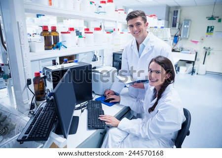 Chemist team working together at desk using computer in the laboratory - stock photo
