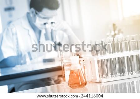 chemist using microscope to analyze the sample at laboratory - stock photo