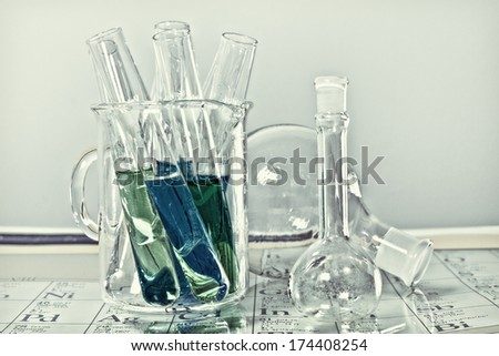 Chemistry glassware with periodic table - stock photo