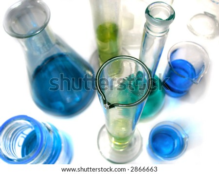 Chemistry laboratory glassware empty and with fluid on white background - stock photo