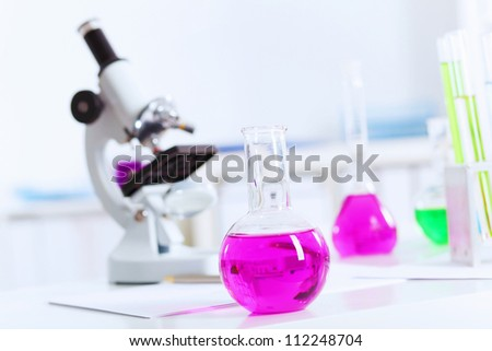 Chemistry laboratory glassware with colour liquids in them - stock photo
